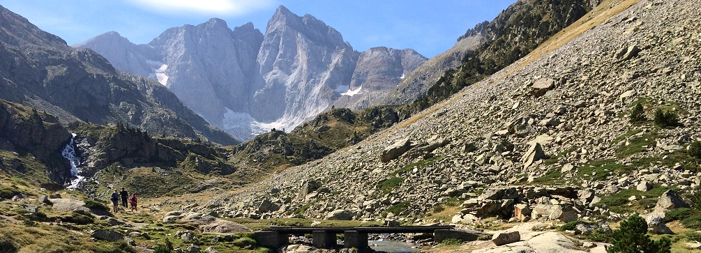 Hikers in the Gaube Valley gaze at the north face of Vignemale, French Pyrenees.